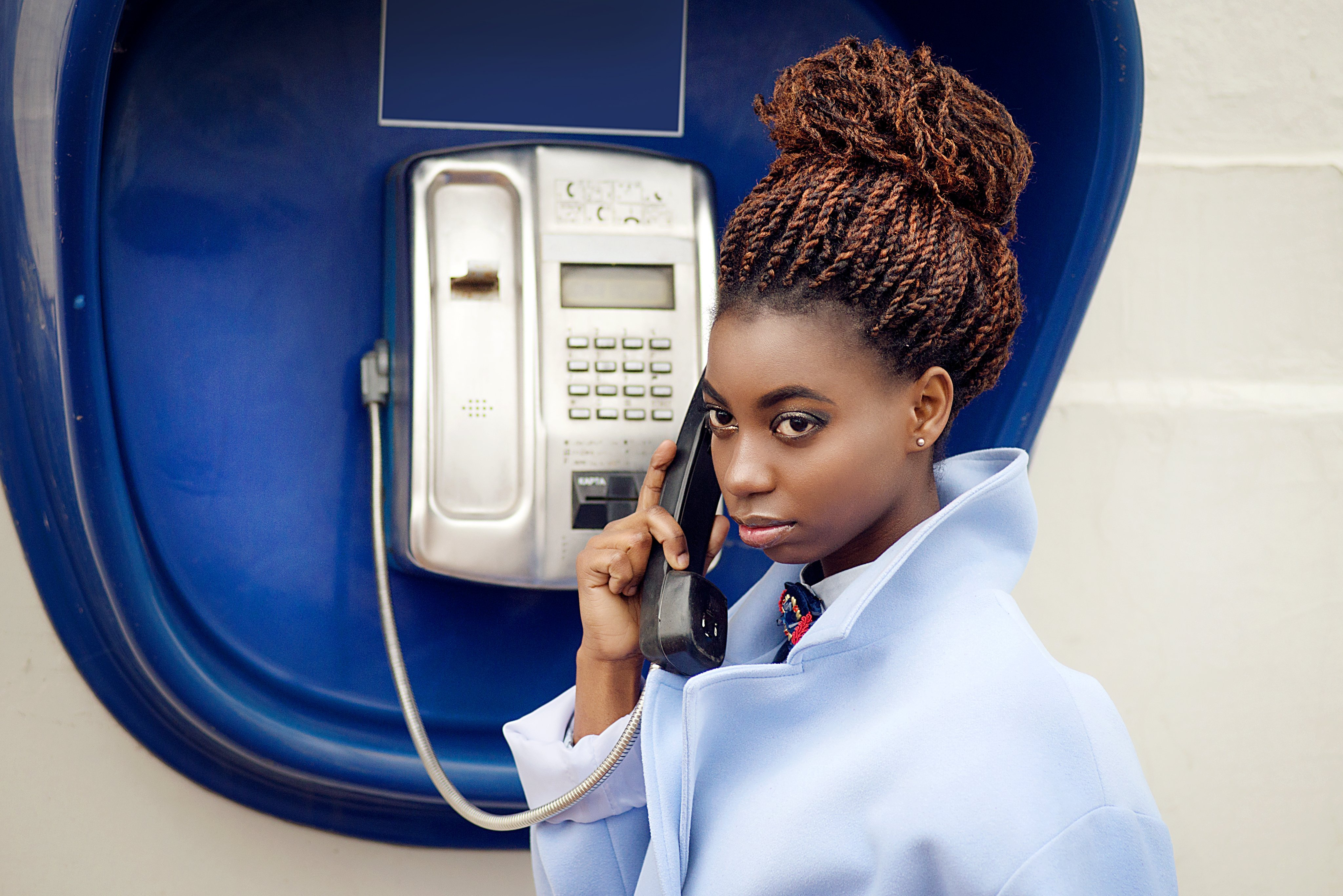 Young girl using a payphone | Photo: Shutterstock
