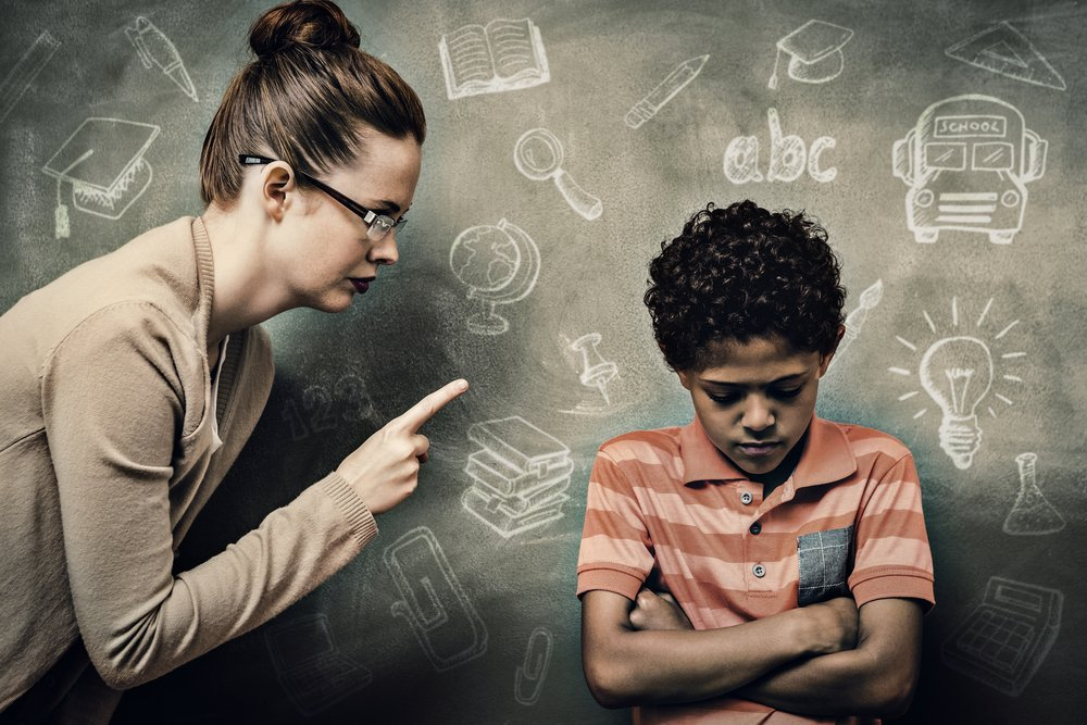 Angry teacher scolding student in front of the classroom. | Photo: Shutterstock.