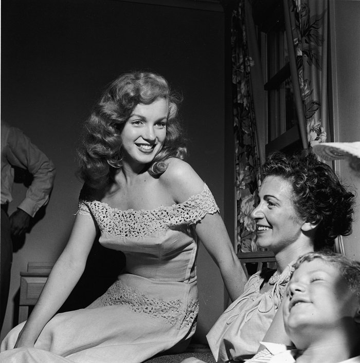 American actor Marilyn Monroe presents Photoplay Magazine's 'Dream House' contest winner Virginia McAllister and her son with the key to a new house, Warrenburg, New York, June 01, 1949. | Photo: Getty Images