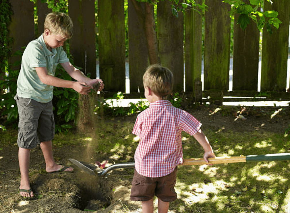 Two young boys help each other to bury a pet in their backyard | Source: Getty Images