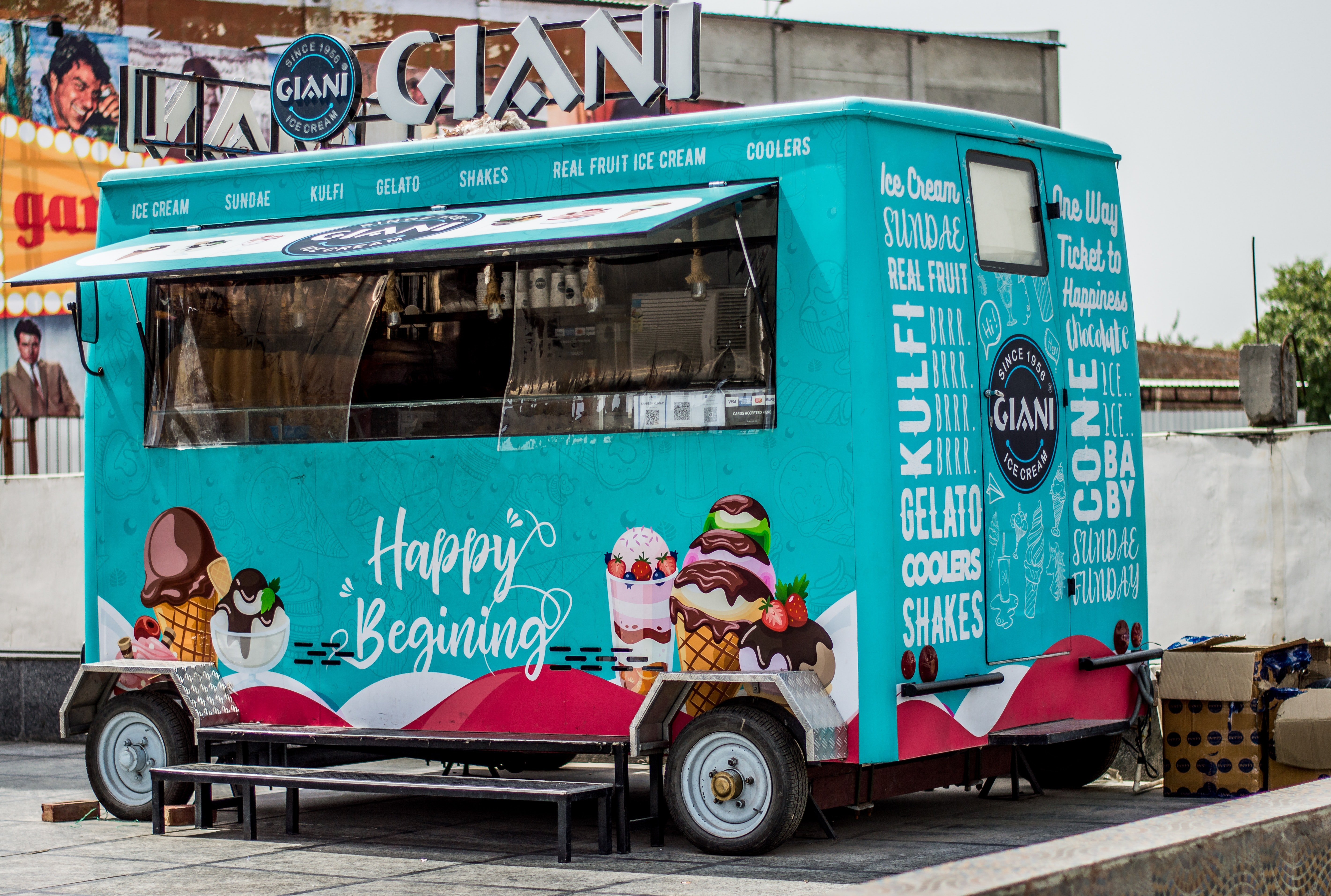 A blue ice cream truck with the words 'Happy Beginning' painted on the side is open for business   Photo: Pexels/Prithpal Bhatia