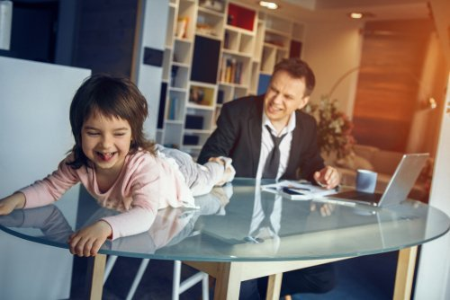 Young daughter playing on the table while her father tries to work. | Source: Shutterstock.