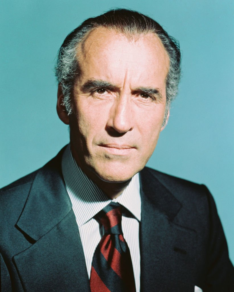 Late Christopher Lee, British actor, wearing a red-and-black striped tie, in a studio portrait, against a light blue background, circa 1970. | Photo: Getty Images