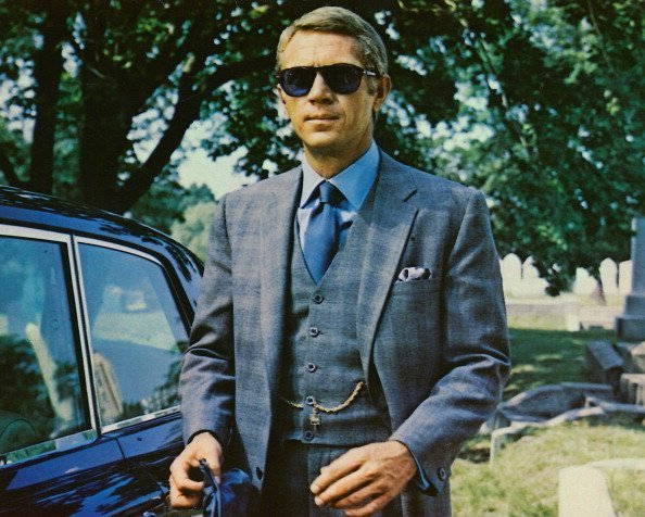 Steve McQueen (1930-1980), US actor, wearing sunglasses with a grey suit, a blue shirt and dark blue tie in a publicity image issued for the film, 'The Thomas Crown Affair', USA, 1968 | Photo: Getty Images