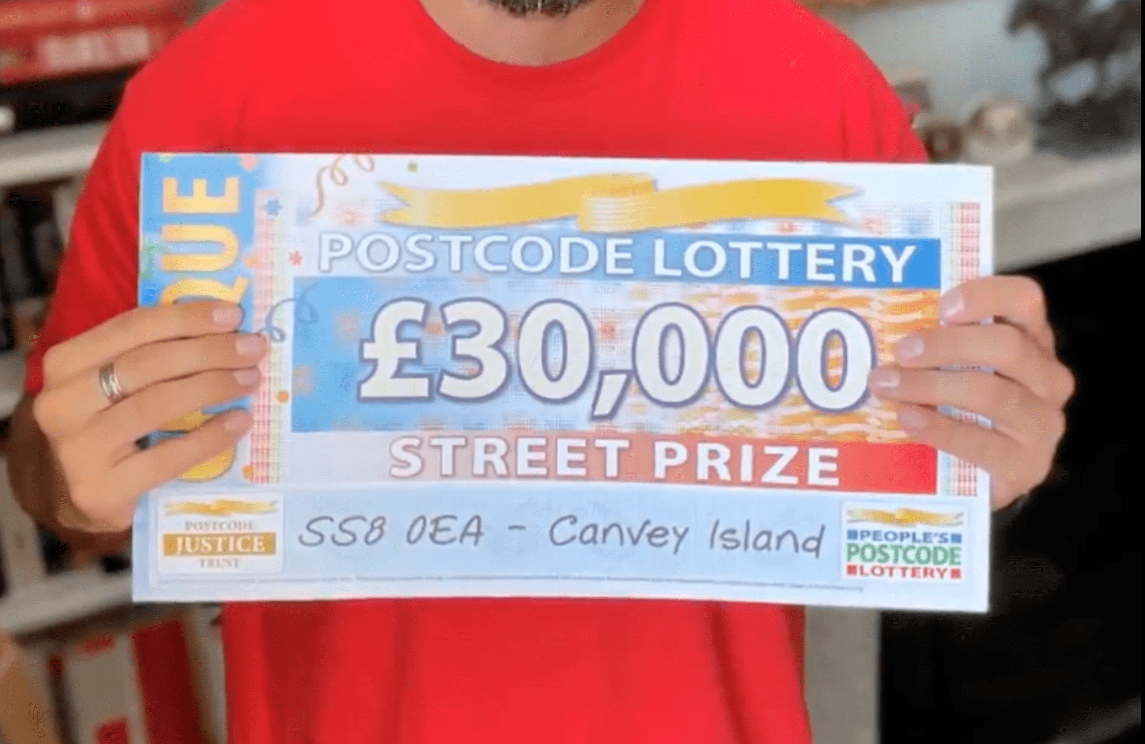 People's Postcode Lottery ambassador holds up a cheque to show a woman that she has won £30,000 (about $41,300) in the lottery   Photo: Twitter/BBCEssex