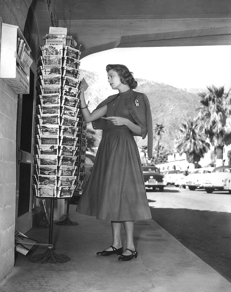 L'actrice Grace Kelly regardant des cartes postales à Palm Springs, Californie en 1954. | Photo : Getty Images