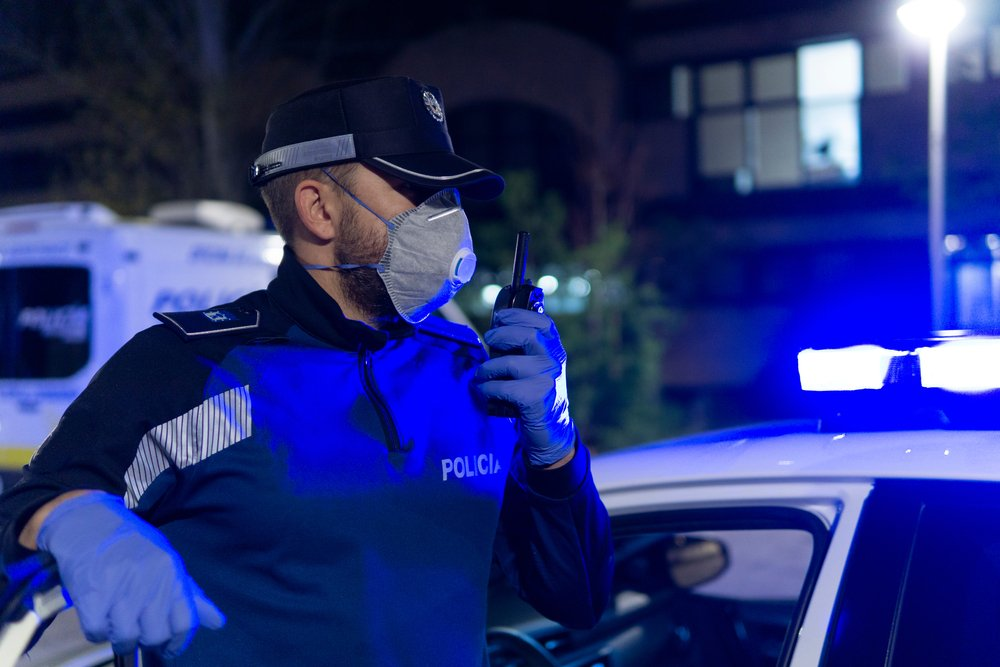 A police officer radioing in a call while wearing a face mask and glovesto protect himself from thecoronavirus   Photo: Shutterstock/Aitana fotografia