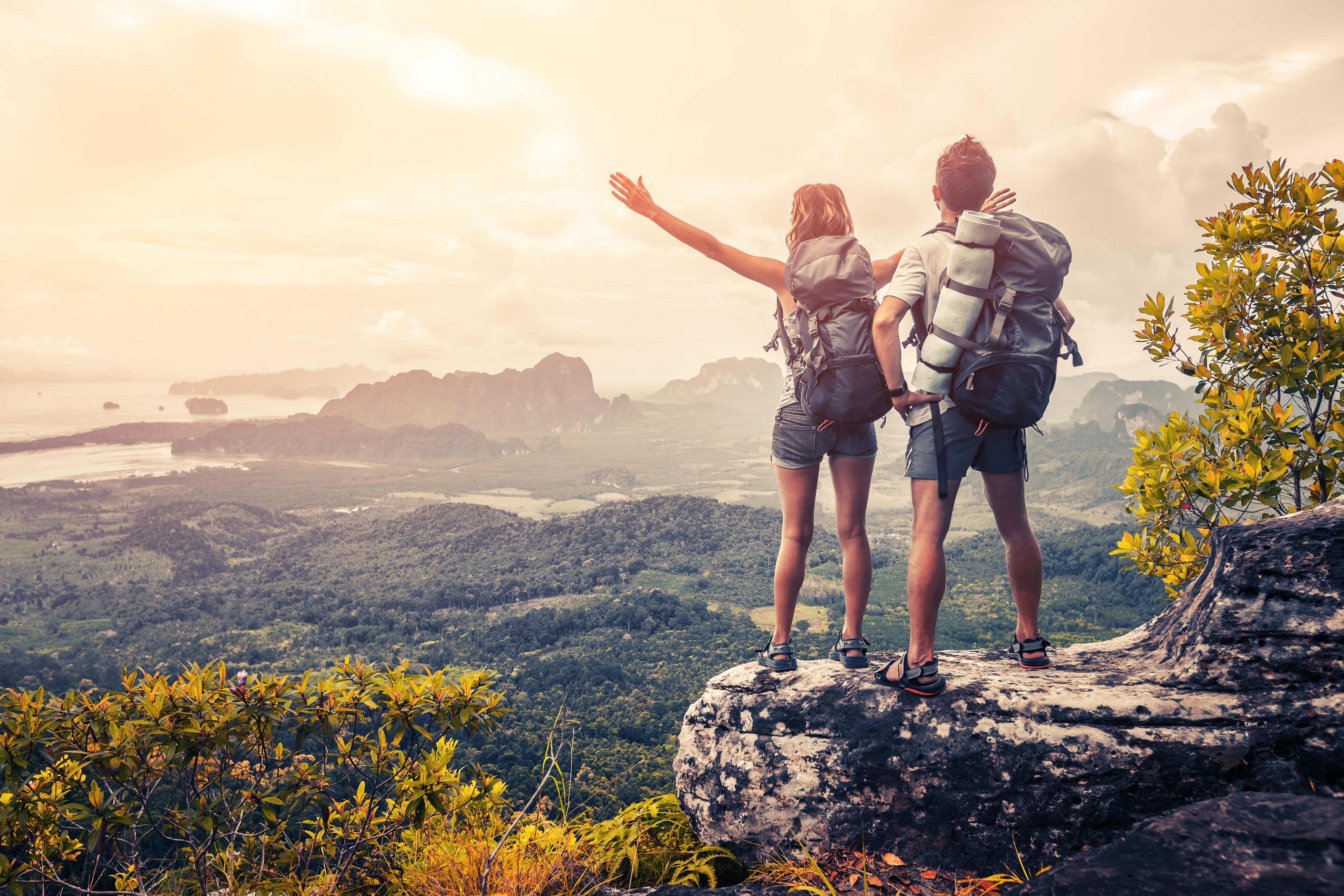 A couple climb a mountain and bask under the sunlight. | Source: Shutterstock