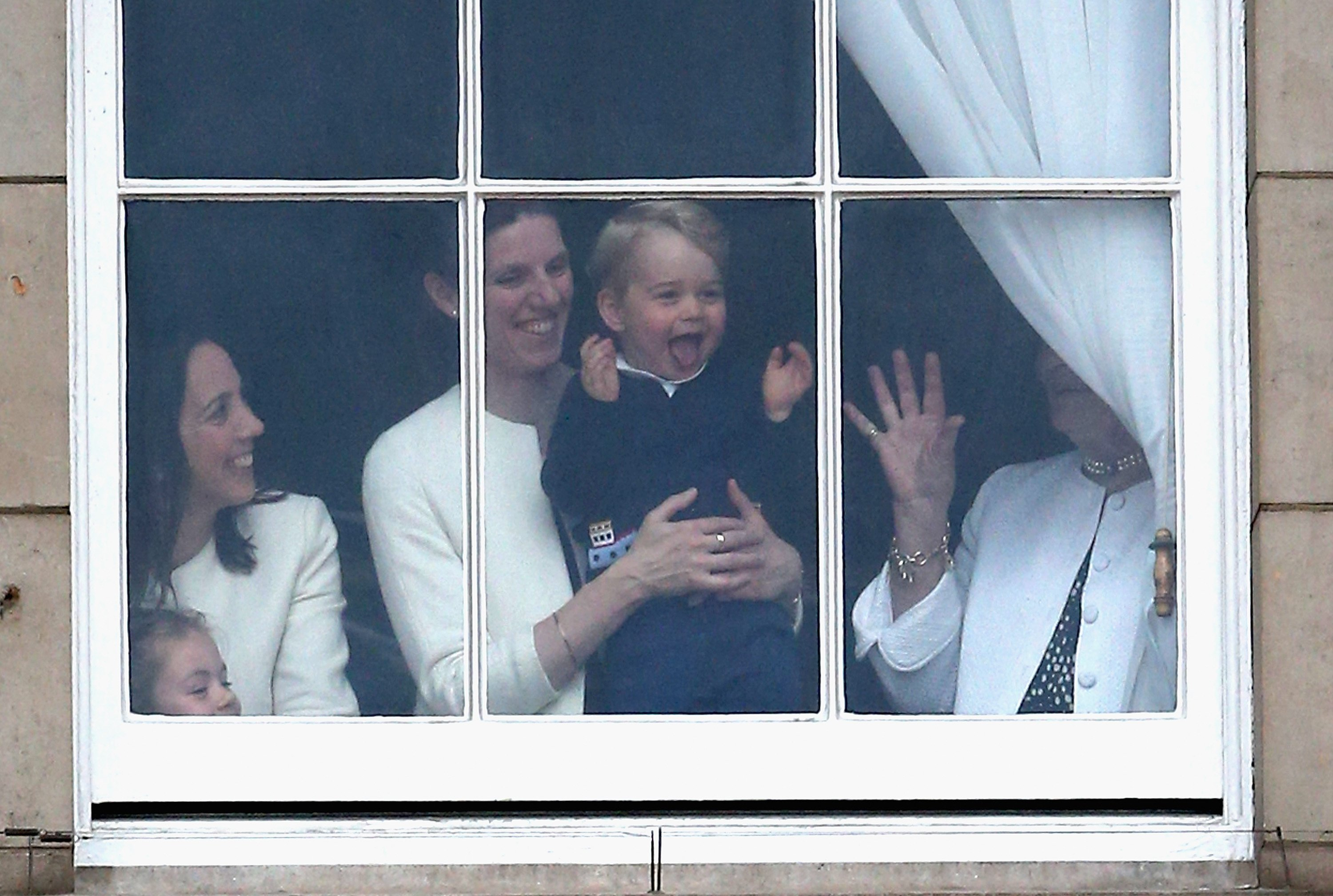 Prince George of Cambridge is held by his nanny Maria Teresa Turrion Borrallo as he waves from the window of Buckingham Palace as he watches the Trooping the Colour on June 13, 2015, in London, England. | Source: Getty Images.