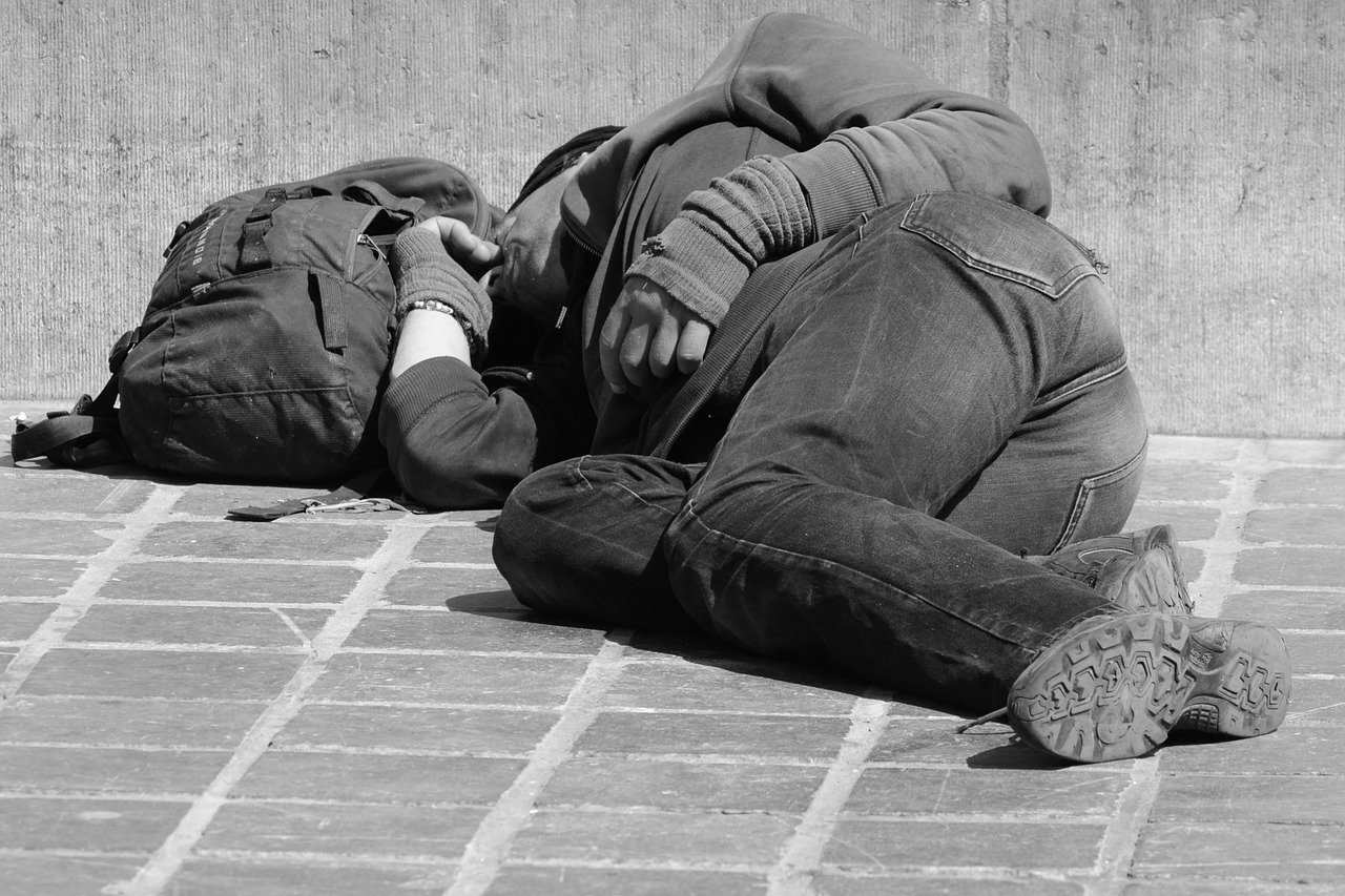 A homeless man lying on the side of the road. | Photo: Pixabay