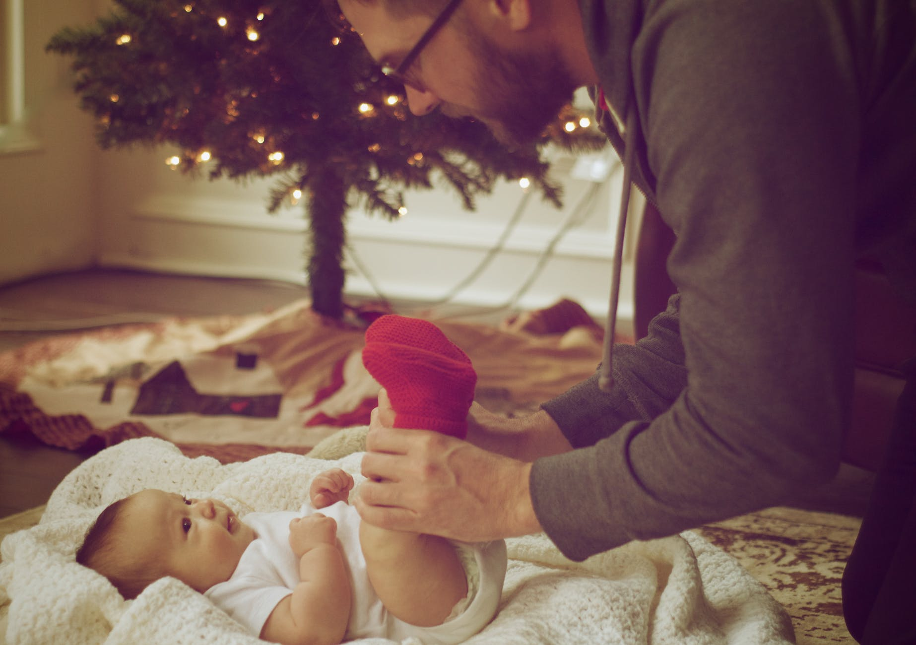 A photo of a doting father taking care of his child and changing diapers. | Photo: Pexels