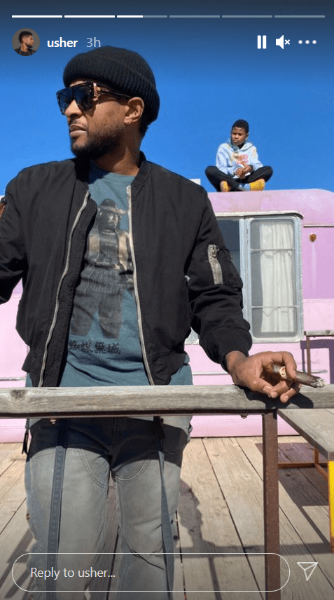 Usher pictured wearing a blacket jacket and head warmer with Cinco behind him sitting on a Cabin.   Photo: Instagram/Usher