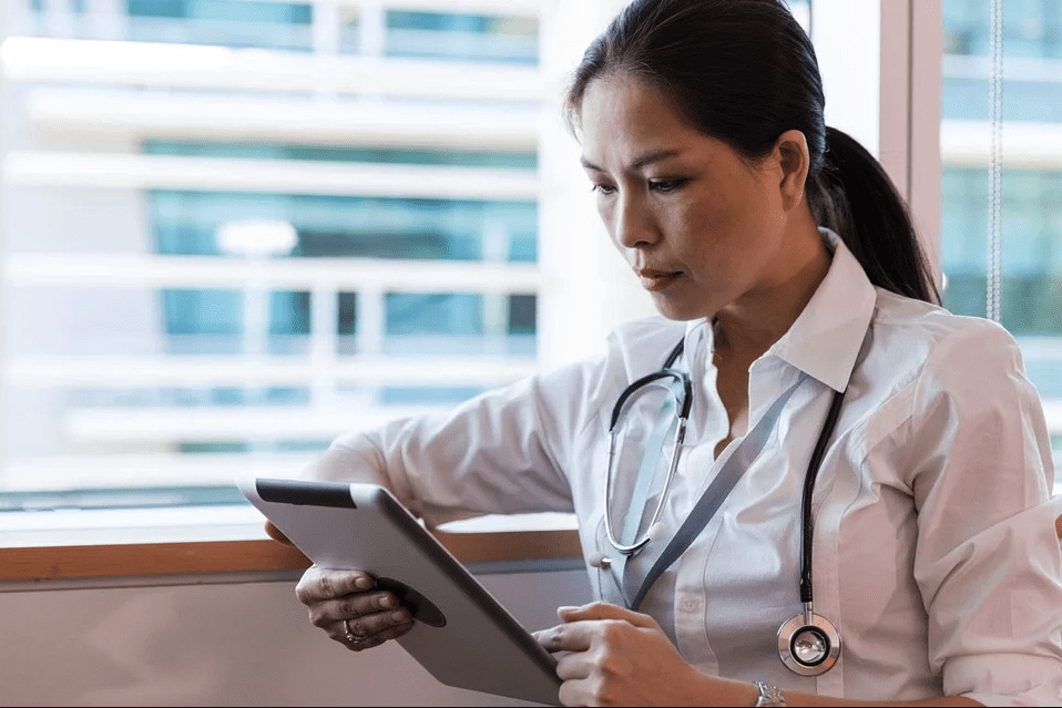 A portait of a doctor going through her tab   Photo: Pixabay