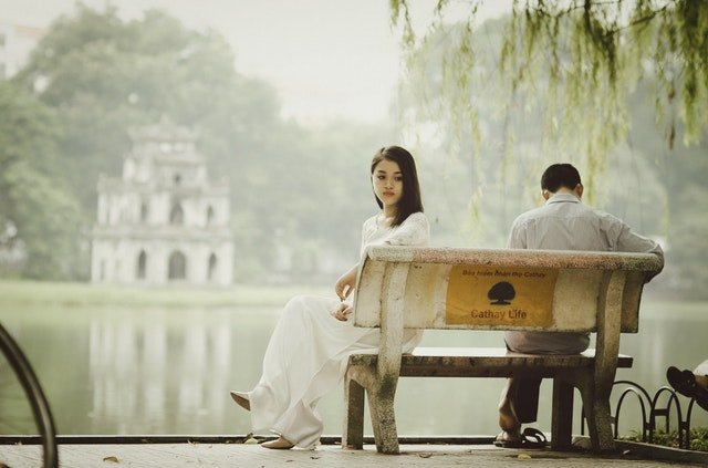 Woman sitting on bench beside a man   Source: Pexels