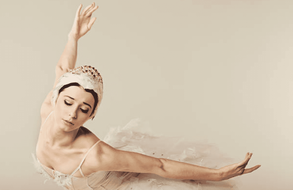 During a performance on stage a ballet dancer wearing a white embellished tutu and tiara leans over and closes her eyes slightly | Source: Getty Images