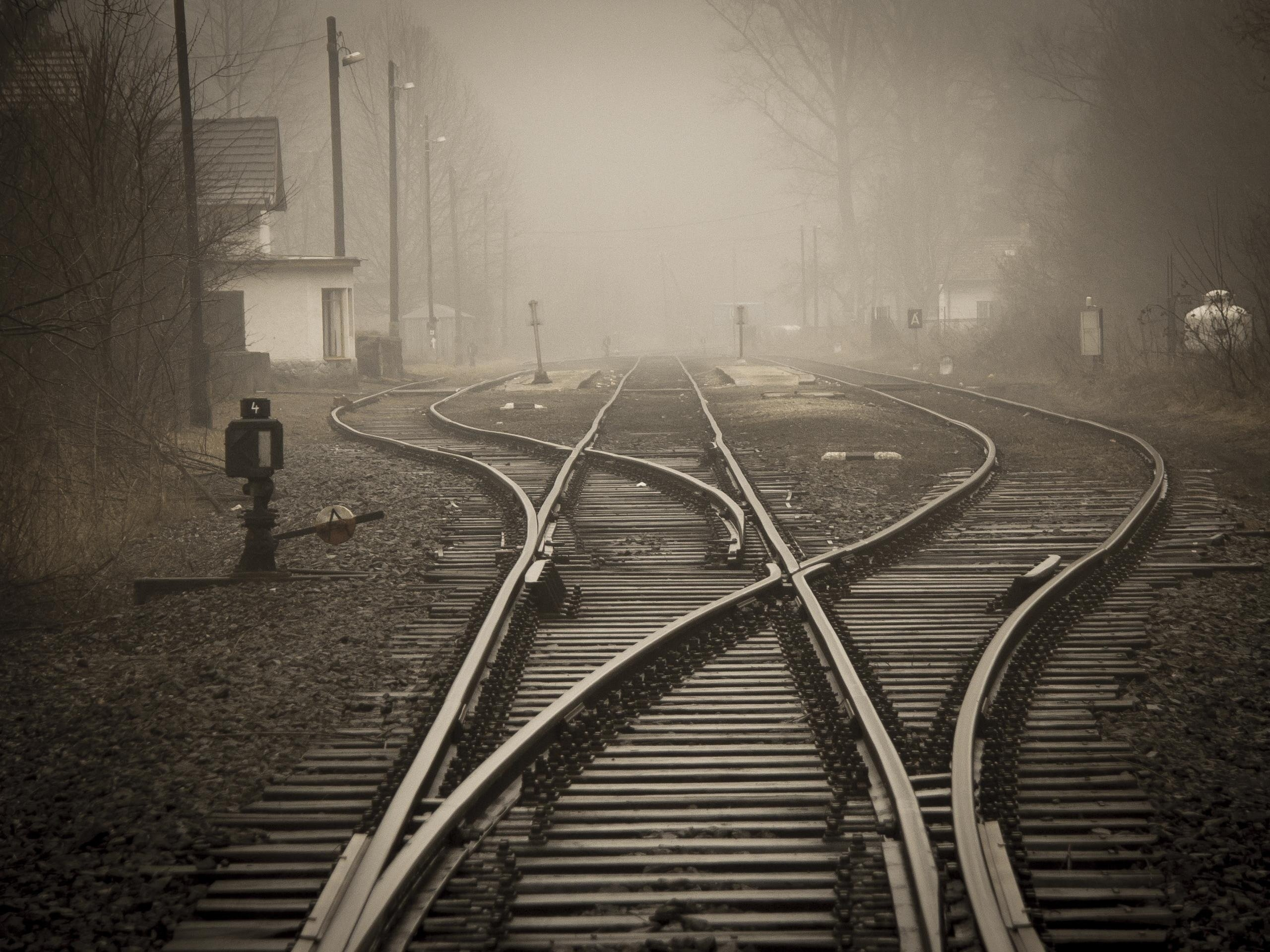 Pictured - An image of railroad tracks in a foggy city | Source: Pexels