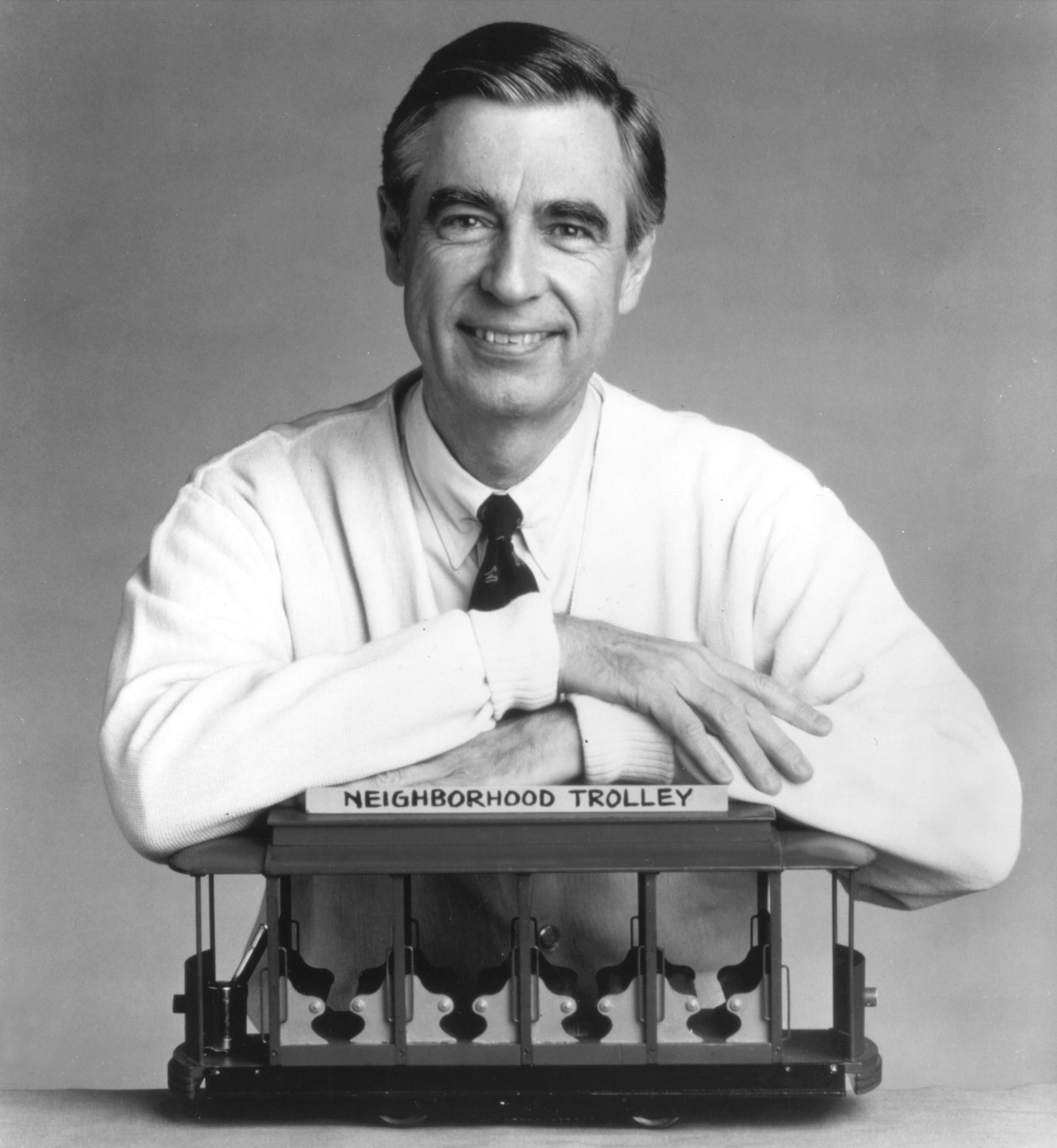 "Fred Rogers, the host of the children's television series, ""Mr. Rogers' Neighborhood,"" rests his arms on a small trolley in this promotional portrait from the 1980's.  
