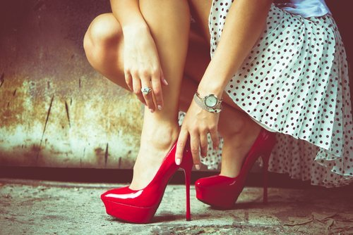 A young woman wearing red high heel shoes. | Source: Shutterstock.