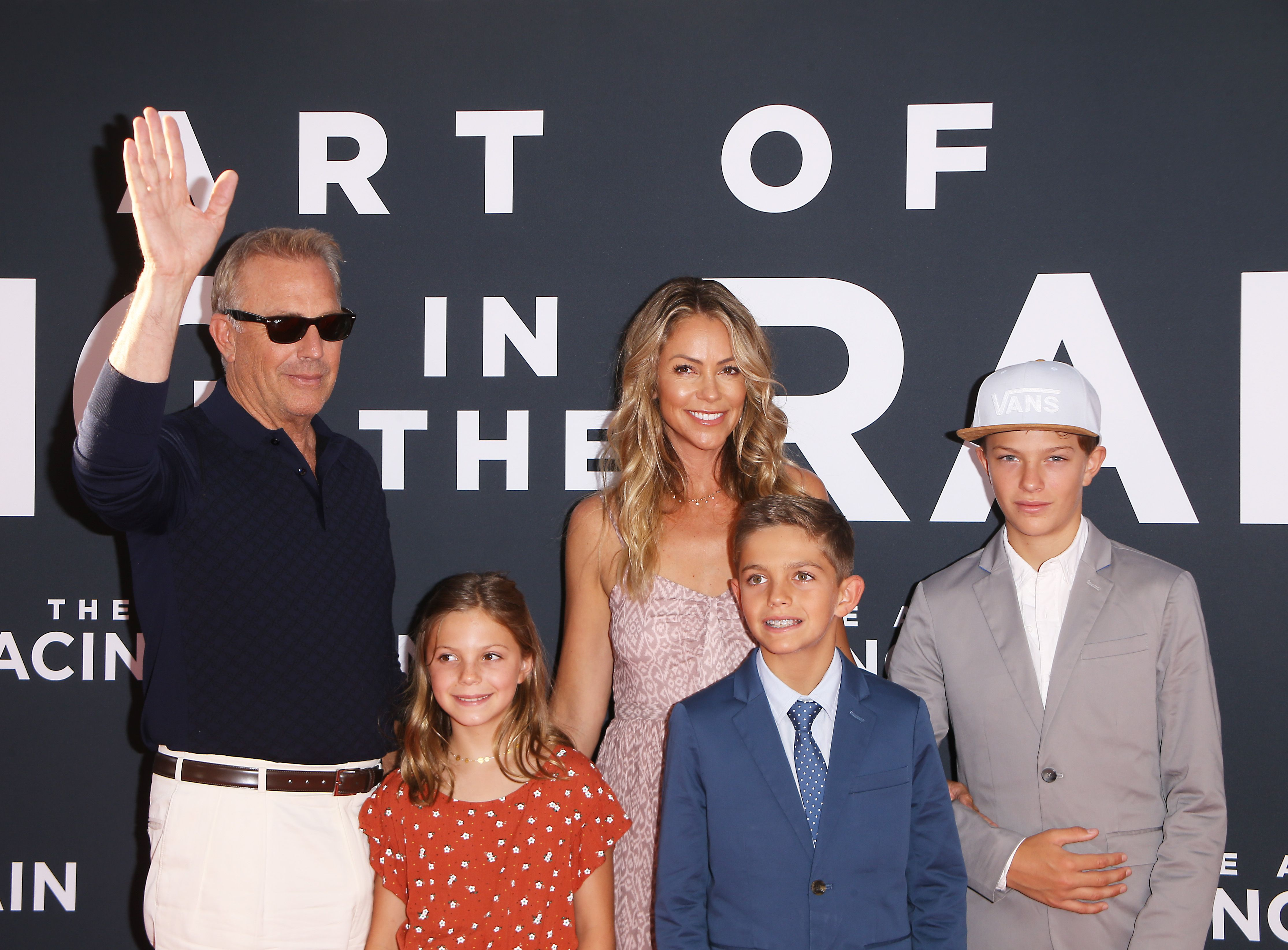"""Kevin Costner, Christine Baumgartner and their kits at the Los Angeles premiere of 20th Century Fox's """"The Art of Racing In The Rain"""" held at El Capitan Theatre on August 01, 2019    Photo: Shutterstock"""