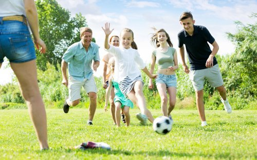 A family playing soccer in the park. | Source: Shutterstock.