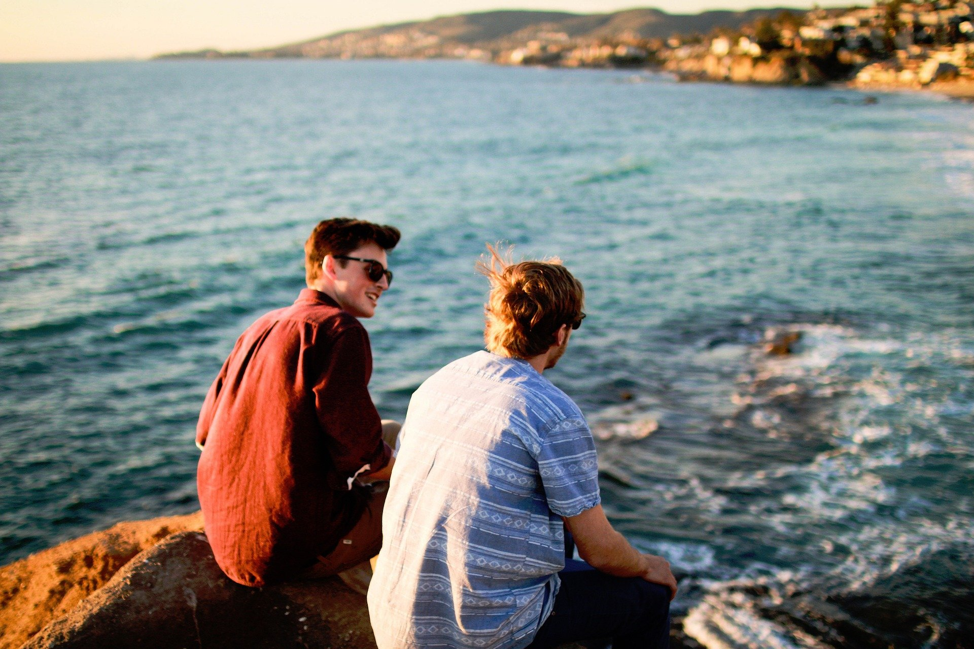 Pictured - Two men conversing while sitting on rocks near the ocean | Source: Pixabay