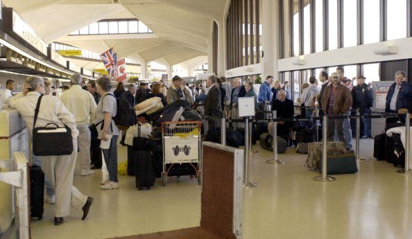 Passengers wait at the American Airlines check-in counter. | Source: Getty Images.