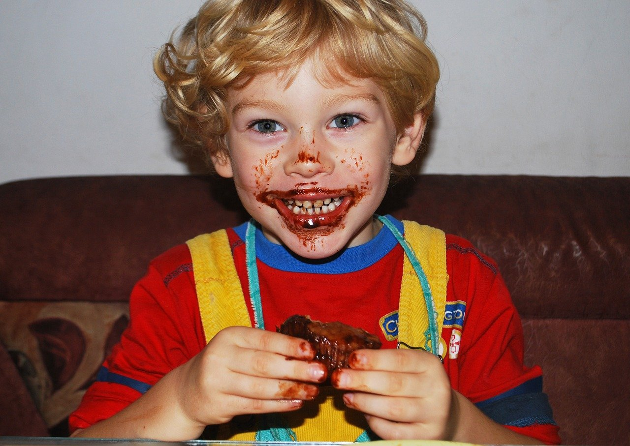A little boy smiling broadly while his mouth is smeared with juices from the meat he's eating | Photo: Pixabay/Mojpe