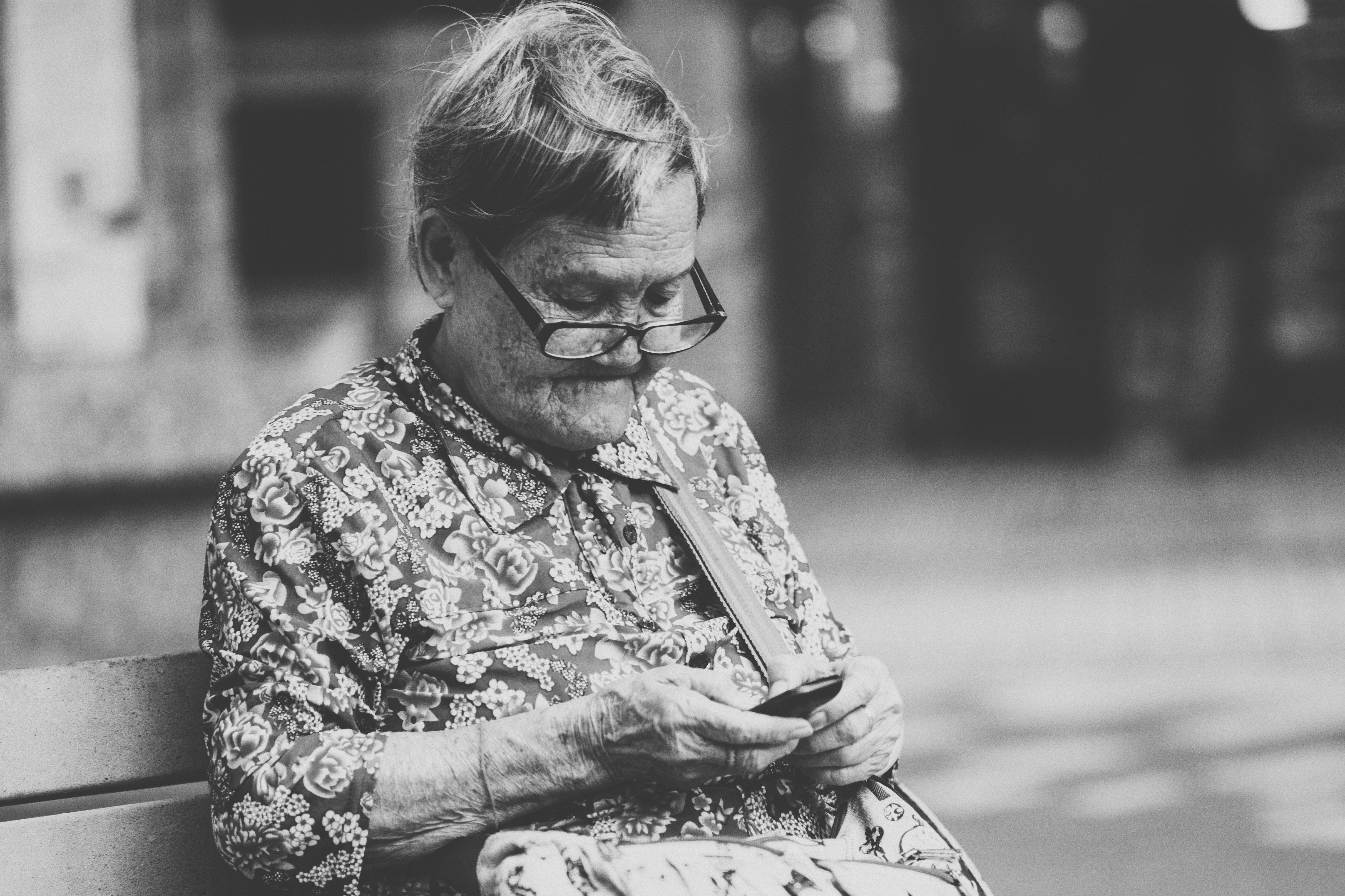 Une Grand-mère assise sur le banc qui utilise un téléphone  | Source : Unsplash