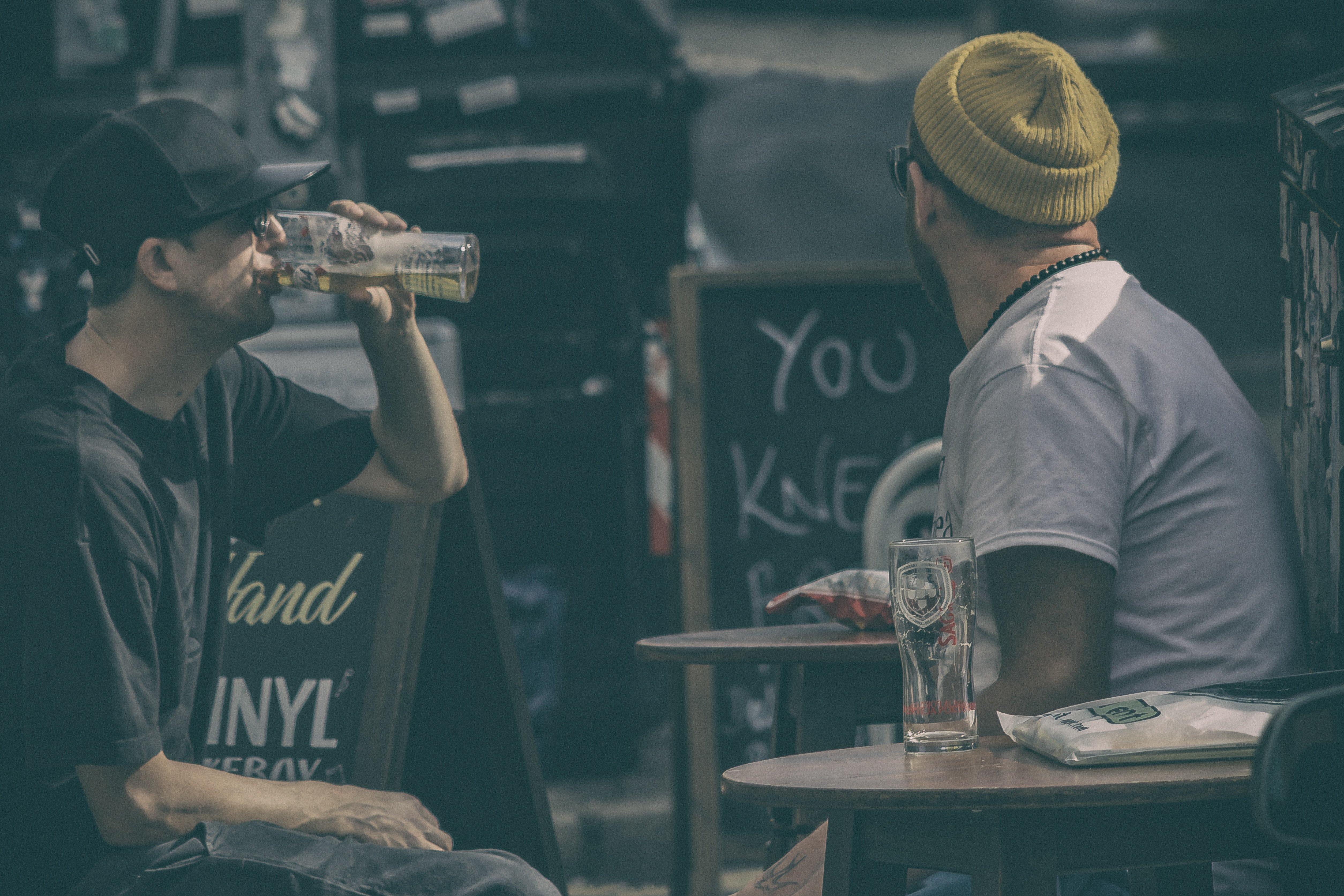 Two men sitting on a table drinking beer. | Source: Unsplash