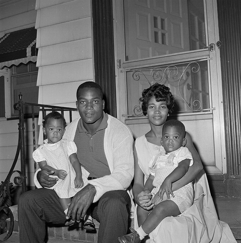Jim Brown, fullback of the Cleveland Browns, sits in front of his home with wife, Sue and twins Kim and Kevin, 19-months-old. I Image: Getty Images.