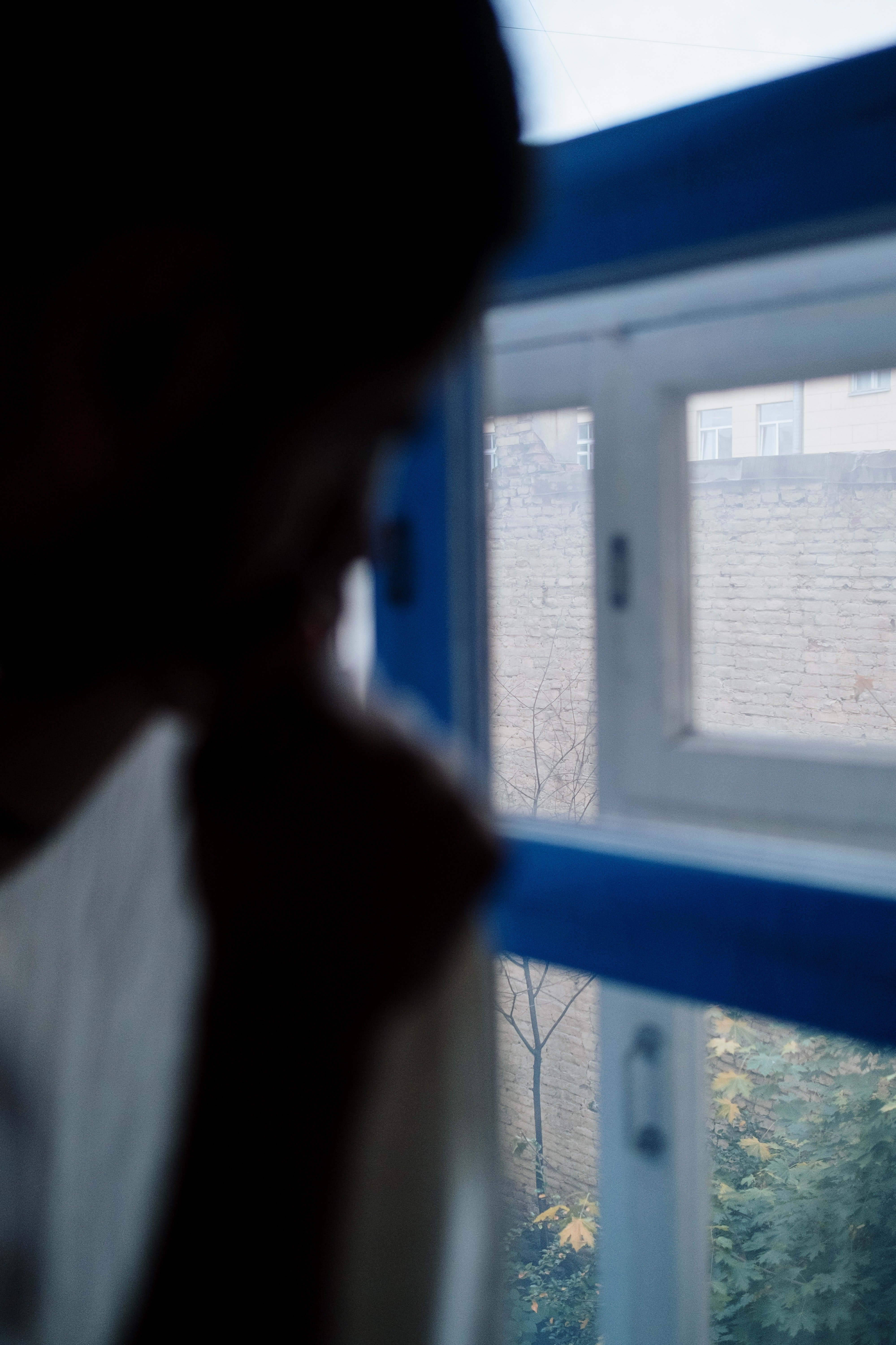 A man pulls back the curtains to peep through a window.   Photo: Pexels.