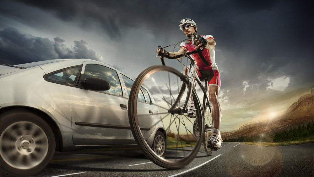 A cyclist driving past a car on a highway | Photo: Shutterstock