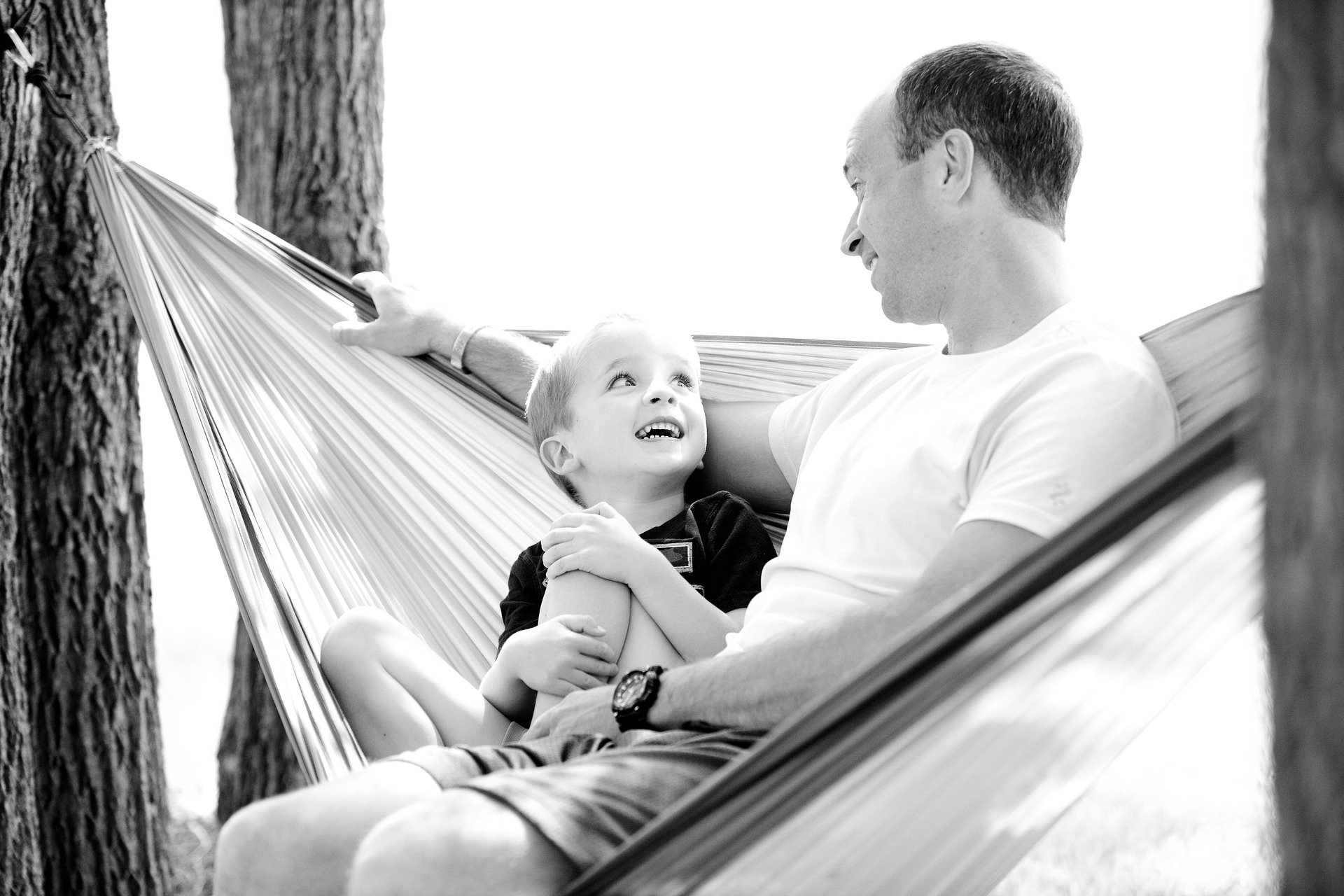 A father and his son sitting together in a hammock. | Source: Pixabay.