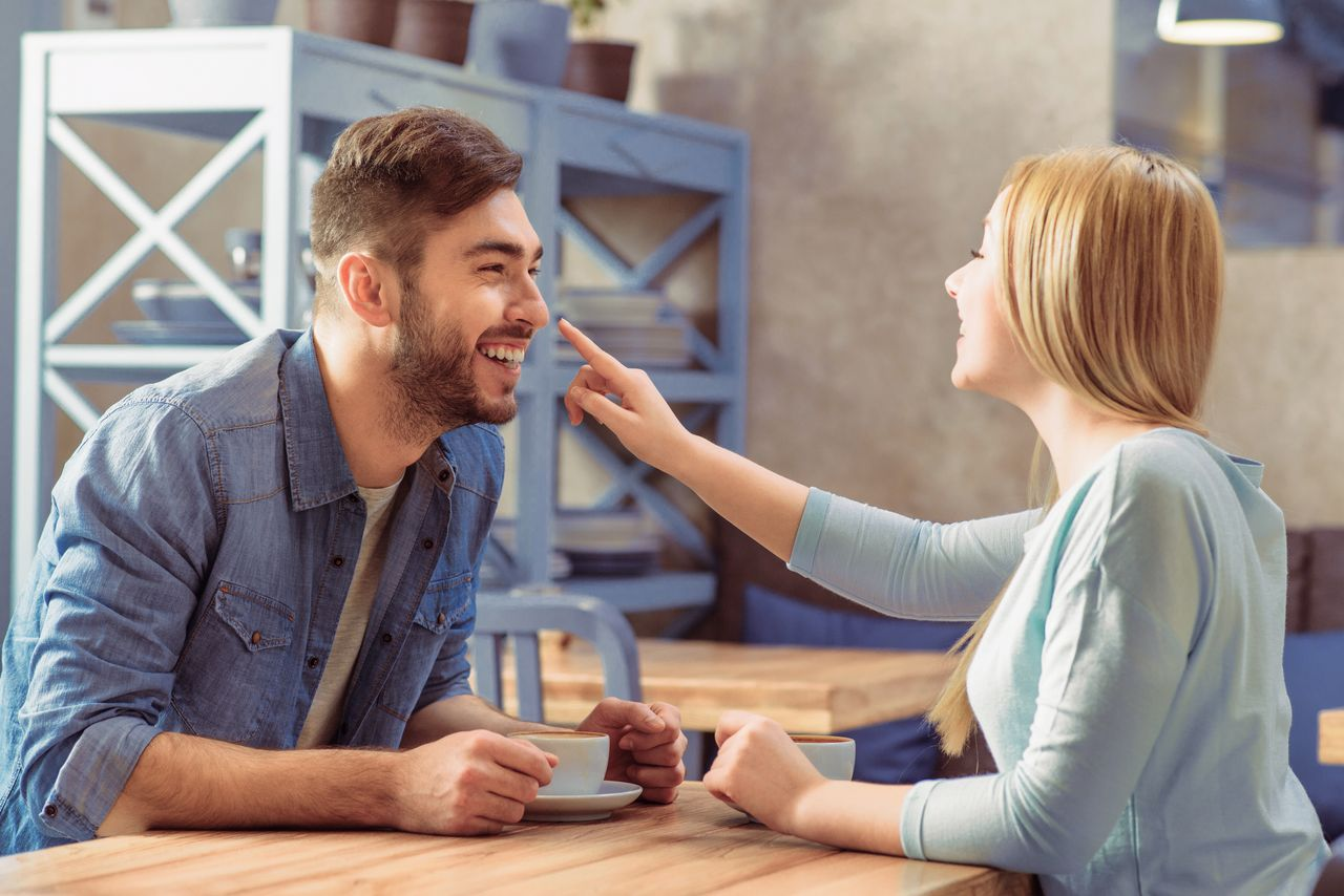 A man and a woman look happy over coffee. | Source: Shutterstock