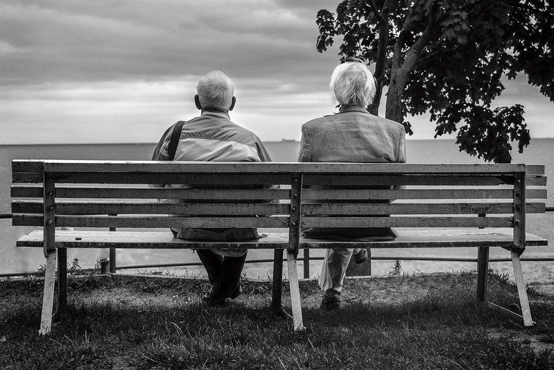 Two old men sitting together on a park bench. | Photo: Flickr