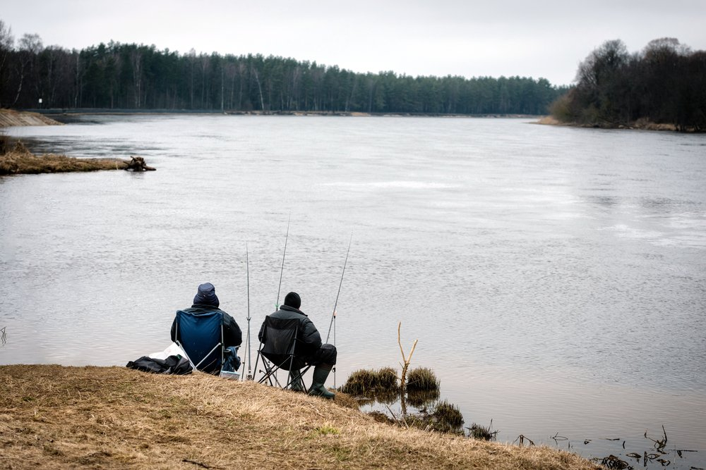 Two people sitting with a pole and catching fish from the lake shore. | Photo: Shutterstock.