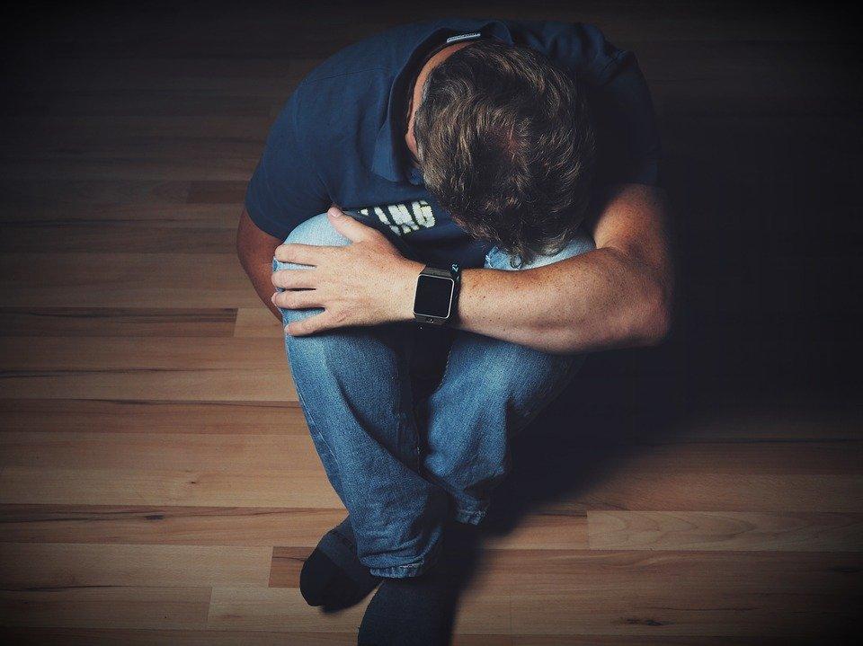 Un jeune homme assis par terre, le visage caché, se plaignant. | Image : Pixabay