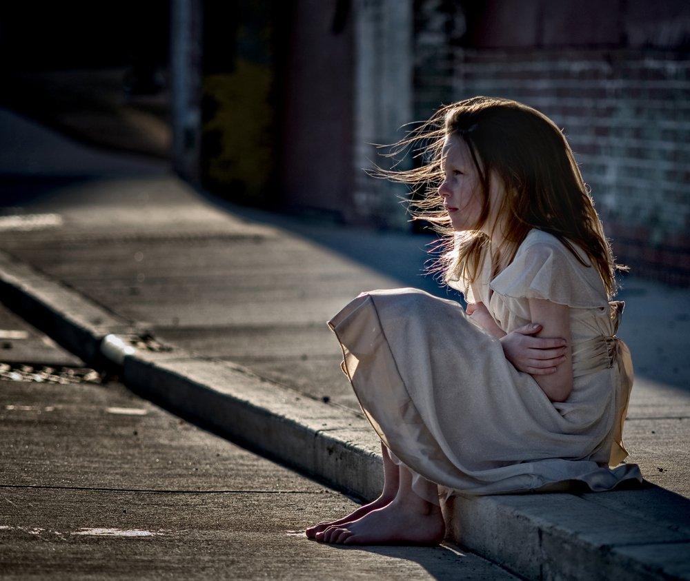 Niña sentada en el bordillo con un vestido sucio. Fuente: Shutterstock