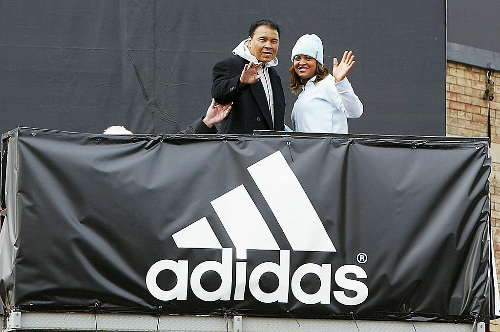 Boxing legend Muhammad Ali poses with his daughter, Laila Ali, as they unveil a new wallscape for addidas | Photo: Getty Images