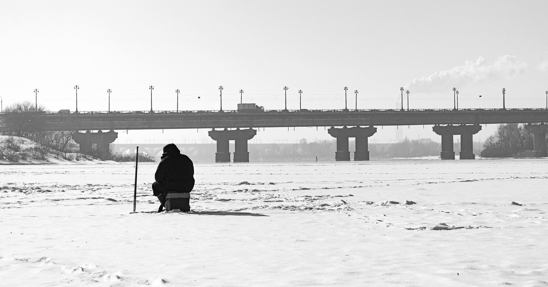 A man ice fishing in a frozen over river. | Photo: Pixabay.