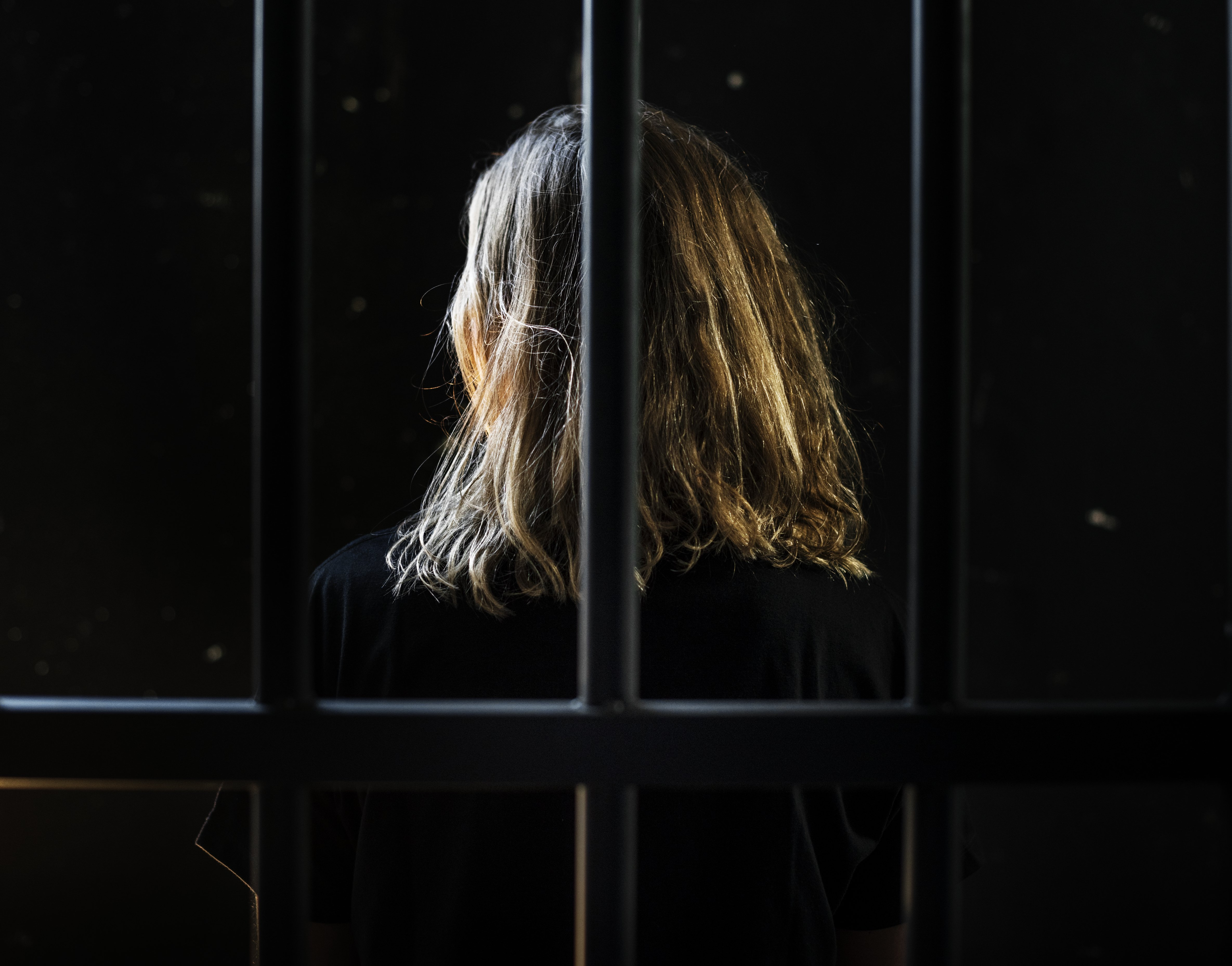 Woman behind bars. | Photo: Shutterstock