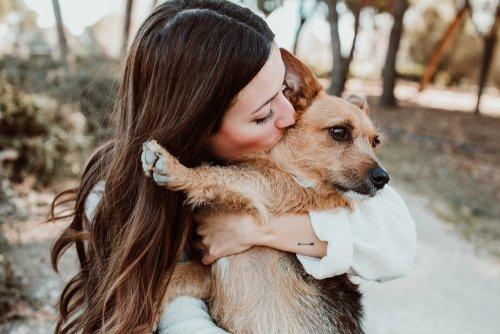 Hermosa mujer jugando al aire libre con su pequeño perro marrón. | Fuente: Shutterstock