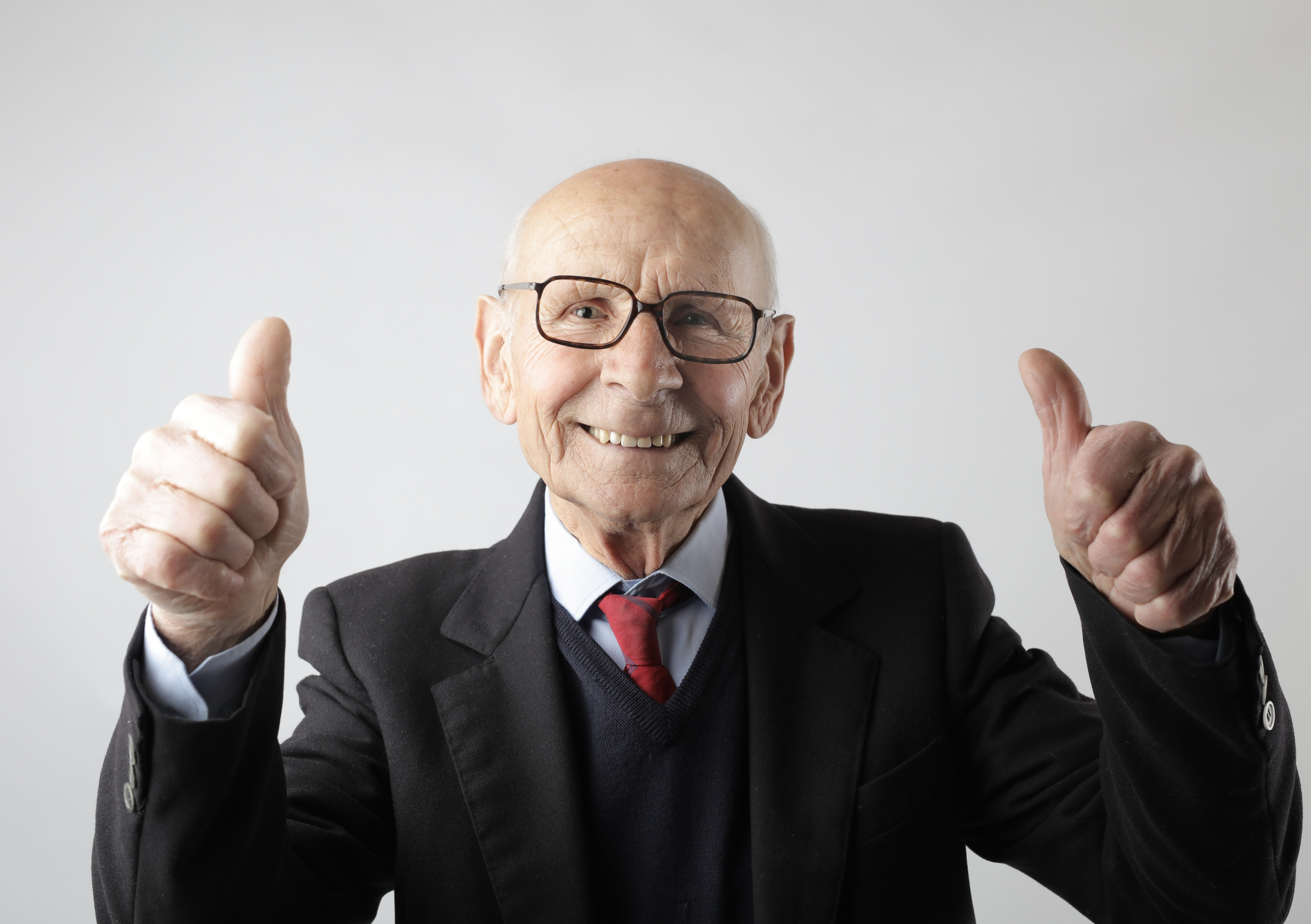 A man in a suit showing two thumbs up.   Photo: Pexels