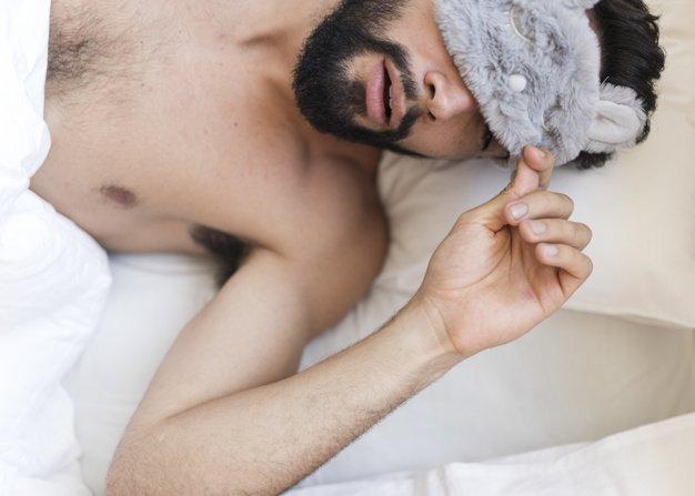 Hombre durmiendo con antifaz tapa ojos. | Imagen: Freepik