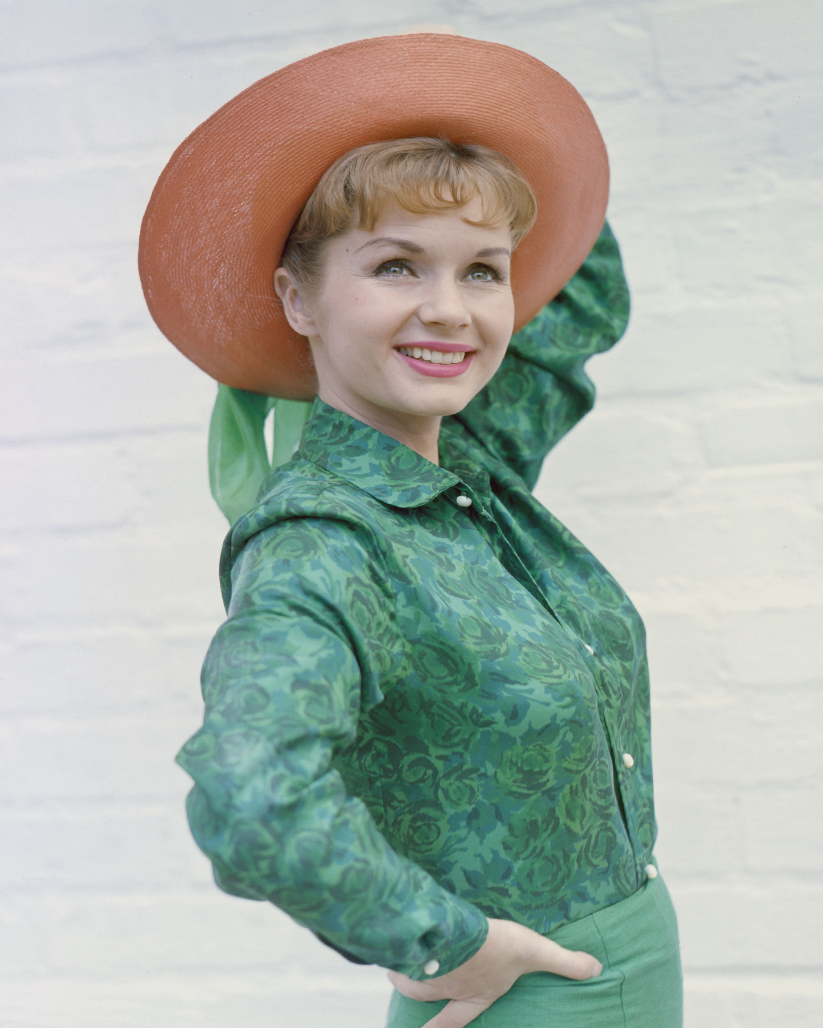 Actress Debbie Reynolds pictured smiling while posing in a green shirt and wide-brimmed salmon pink hat on January 01, 1960 | Photo: Getty Images