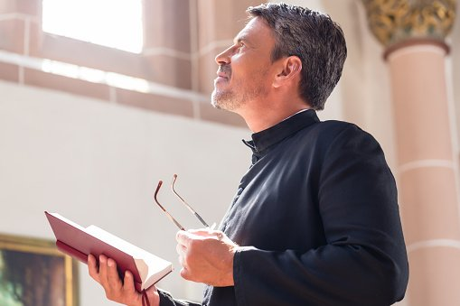Photo of a priest looking away while holding a bible | Photo: Getty Images