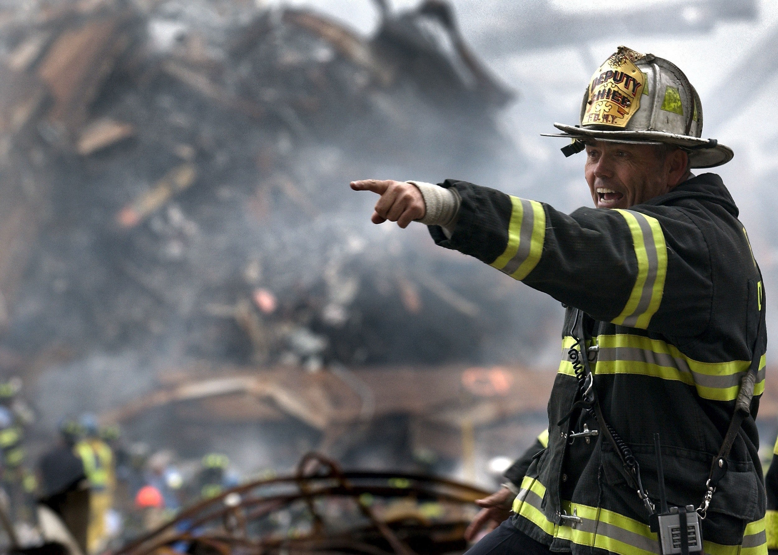 Pictured - A firefighter wearing a black and yellow uniform pointing   Source: Pexels