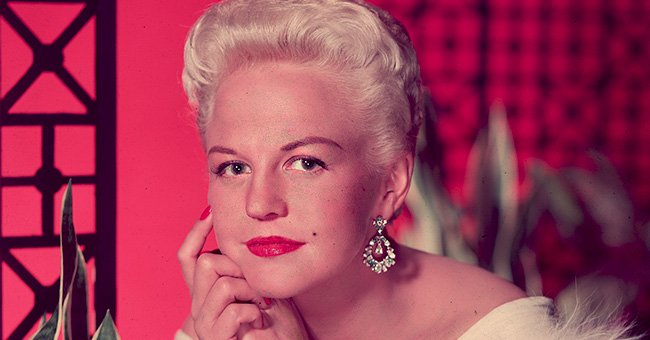 Studio portrait of singer Peggy Lee (1920 - 2002) wearing a fur- trimmed white gown and diamond earrings | Photo: Getty Images