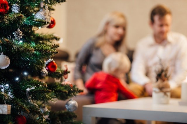 A family enjoying the holidays with a Christmas tree next to them | Colleagues having a drink together on Christmas | Source: Pexels