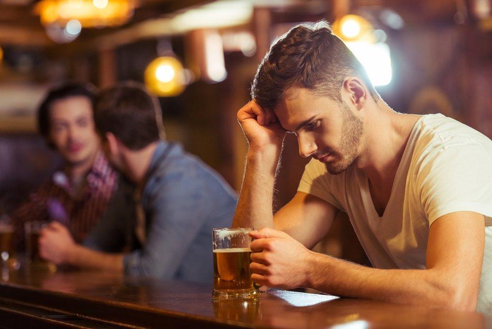 Hombre con camiseta blanca mirando un vaso de cerveza mientras está sentado en la barra de un bar. | Imagen: Shutterstock